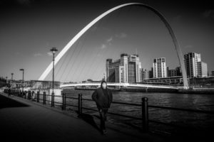 Person walking down the quayside Newcastle with mask on
