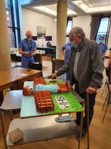 Keith Yeomans cutting the Angel of the North cake he presented to NHS staff on Critical Care unit