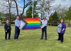 Medical director Andy Welch raises the pride progress flag at the Freeman Hospital with other members of staff