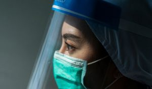 Staff member in mask and visor looking into the distance
